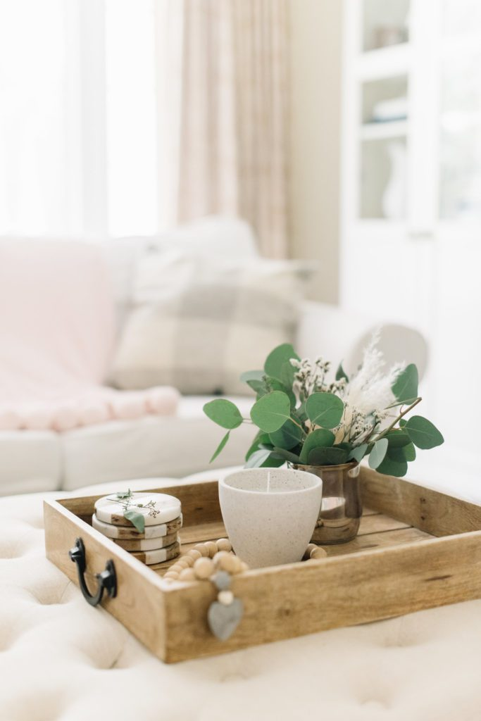 A living room filled with furniture and vase of flowers on wooden tray
