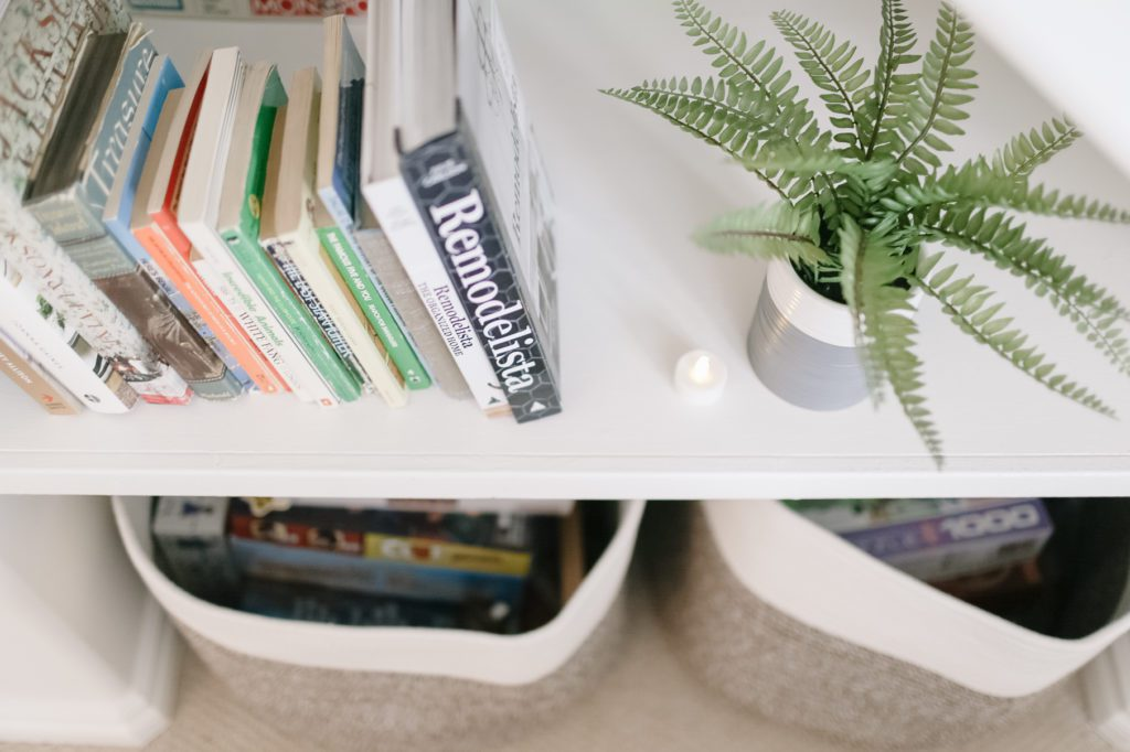 stacked books on a shelf with games underneath