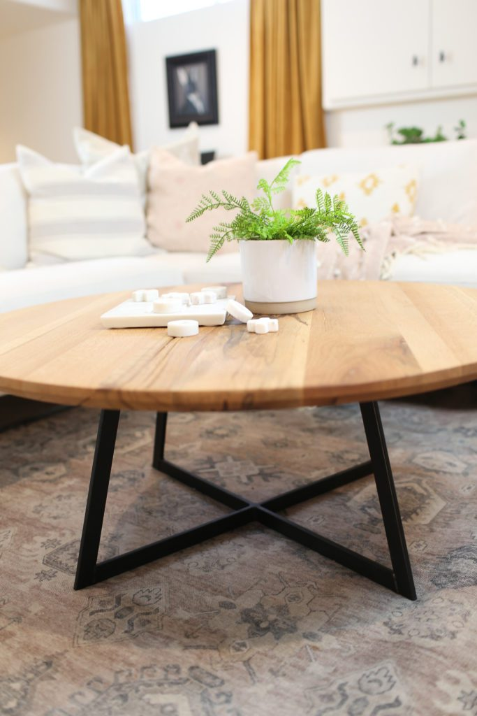 wooden coffee table with a fern on top and black metal legs
