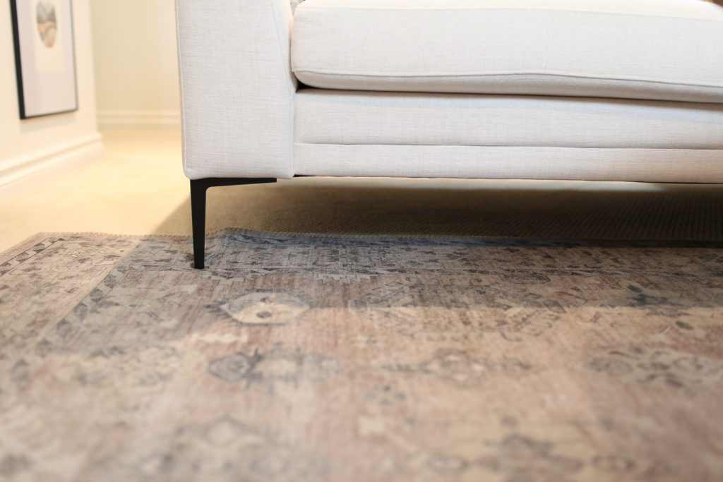 pink patterned rug under a sectional with black metal legs