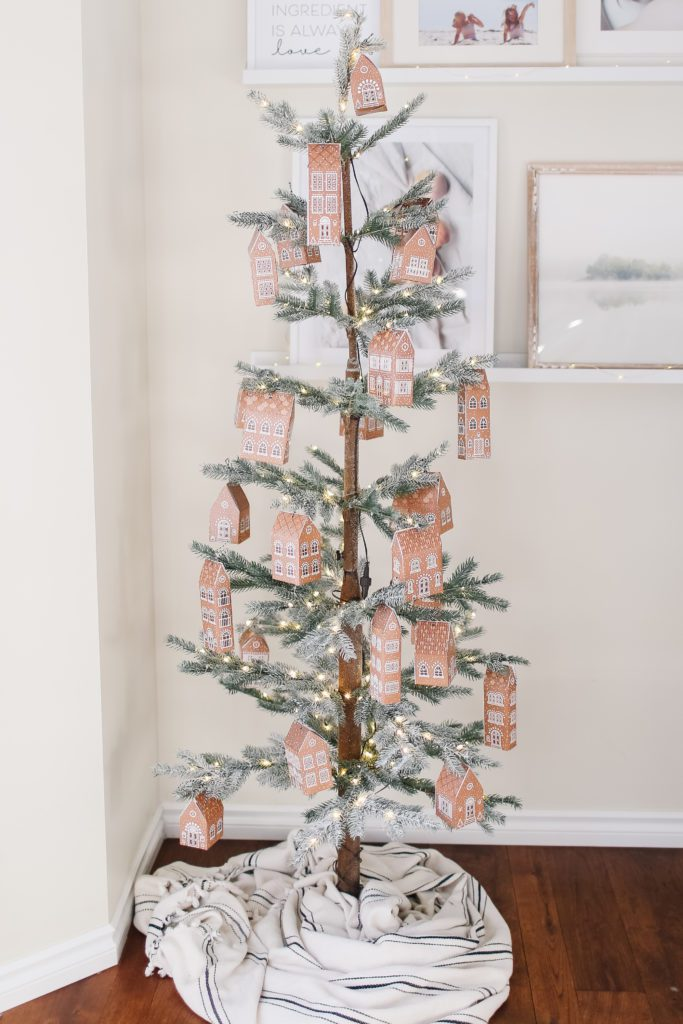 A Christmas tree with gingerbread house boxes hanging on it