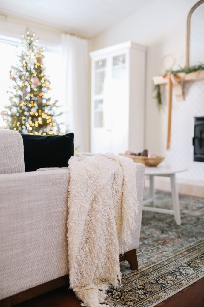 A white throw blanket on the side of a couch