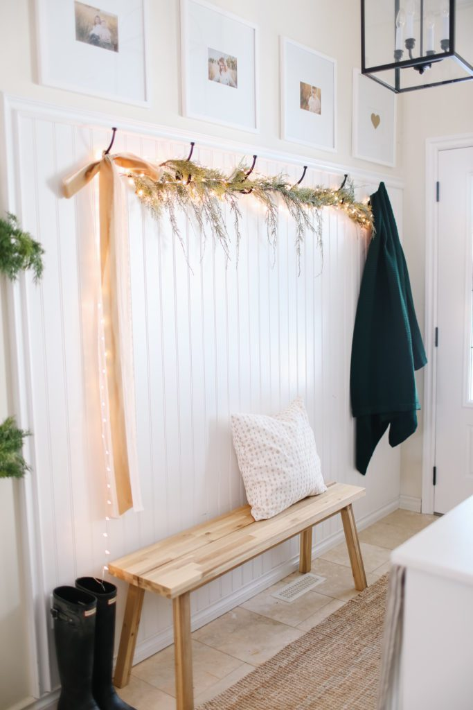 A front entry with greens, lights and ribbon hung across the coat hooks