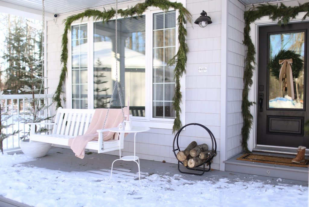 A window hung with garland and a blanket on a front porch swing