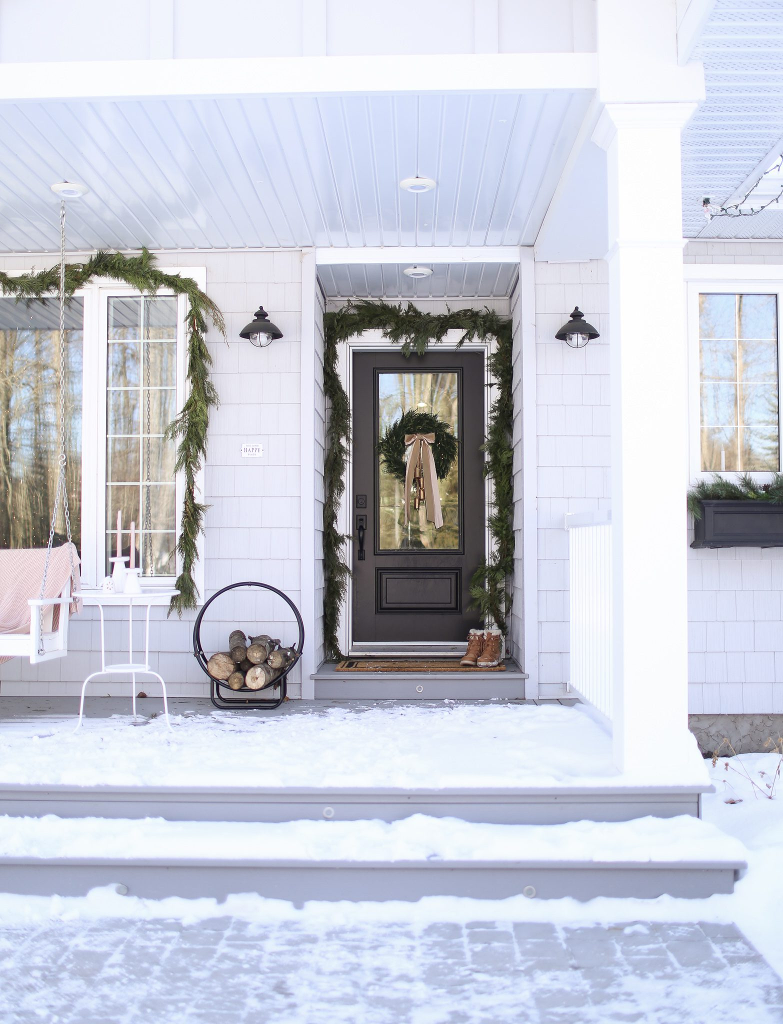 A snowy front porch decorated for Christmas