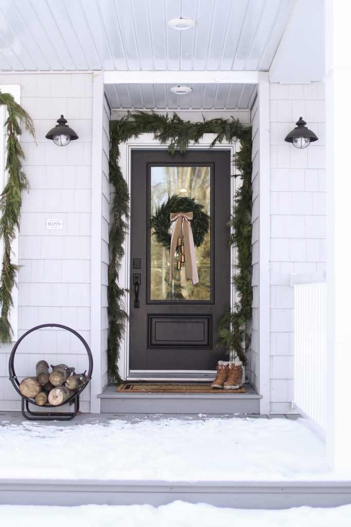 A black front door decorated for Christmas with fresh garland and wreath