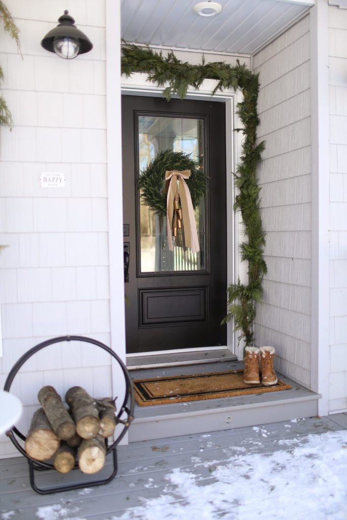 A black front door with a Christmas wreath and a round log holder