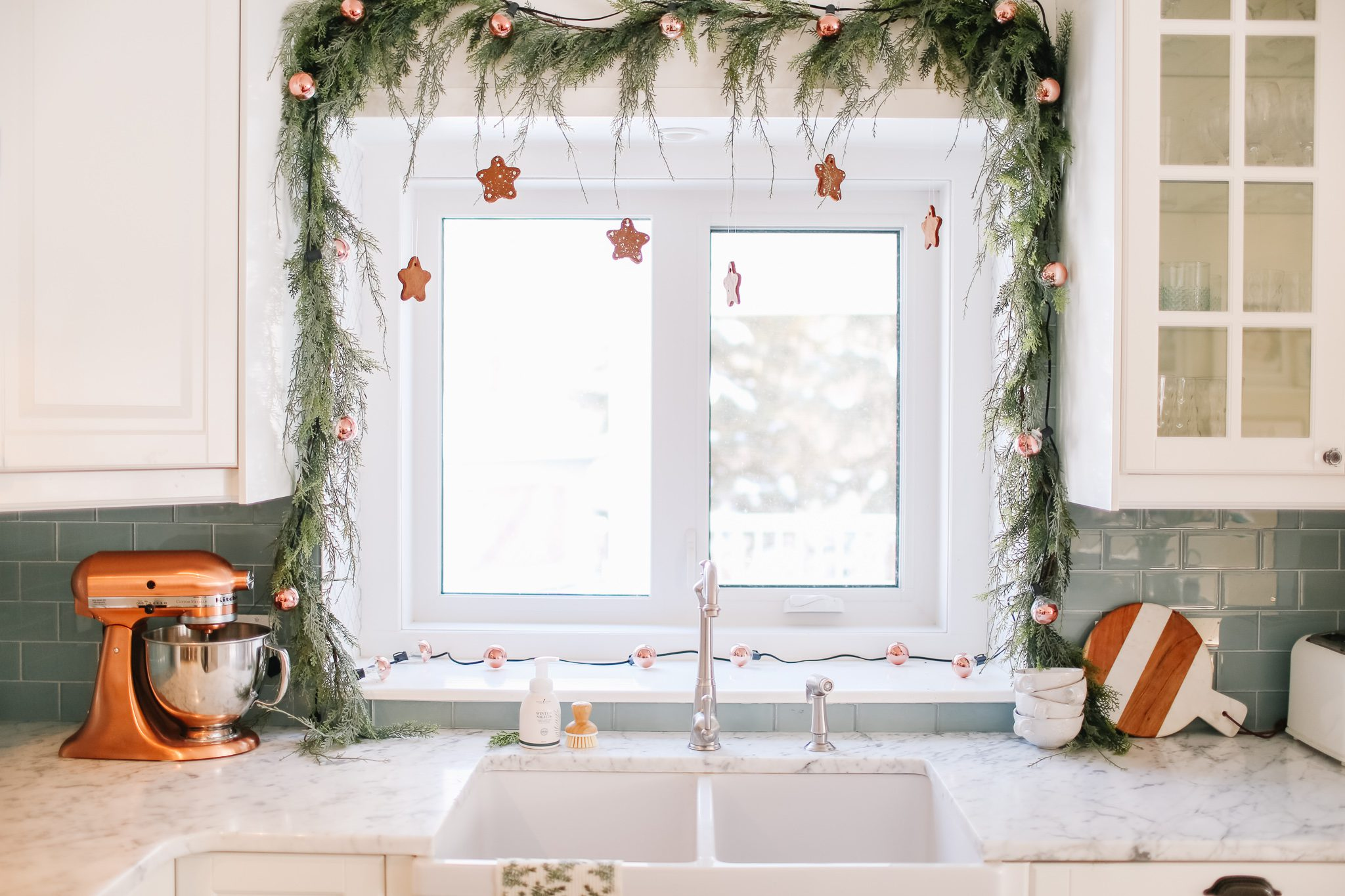 kitchen window decorated with Christmas garland and gingerbread cookies shaped like stars