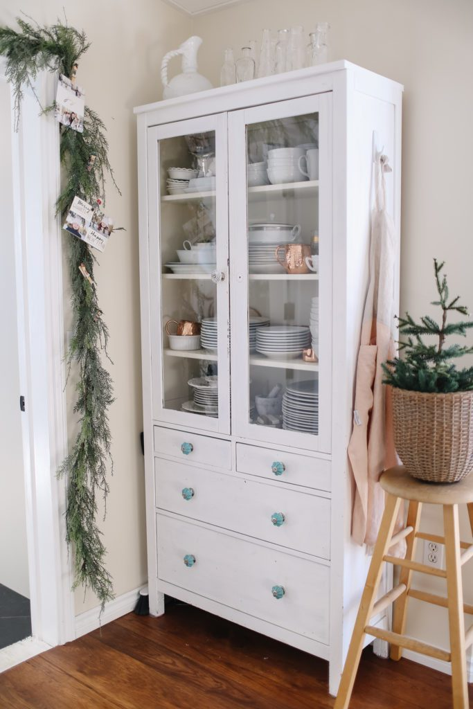 Hutch full of white dishes with Christmas garland