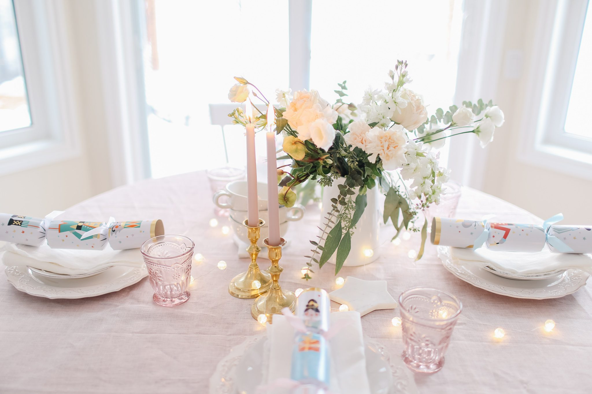 A vase of flowers on a table with fairly lights and candles