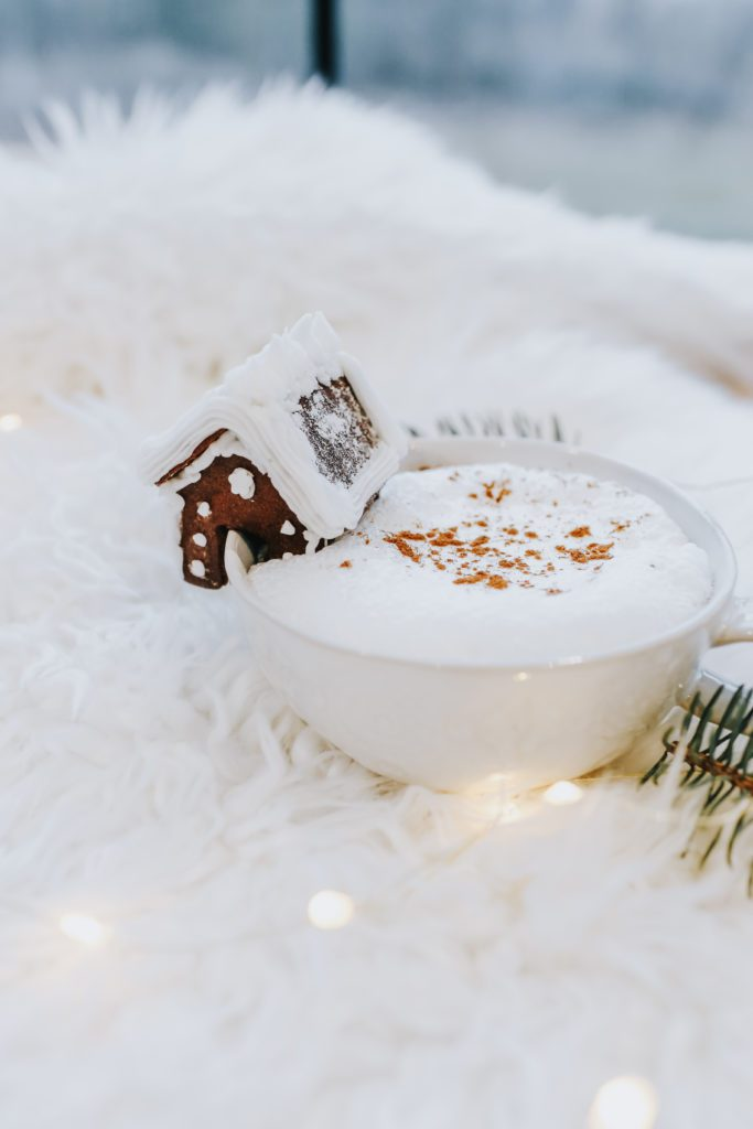 A plate with a piece of cake covered in snow, with Gingerbread and Mug