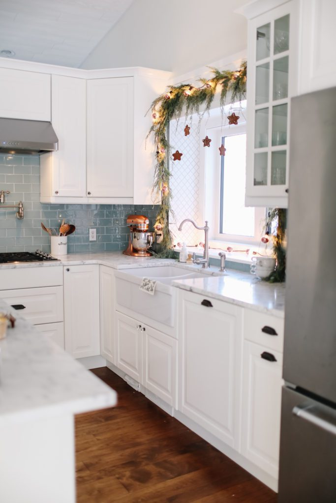 white kitchen with copper lights, and garland over the window
