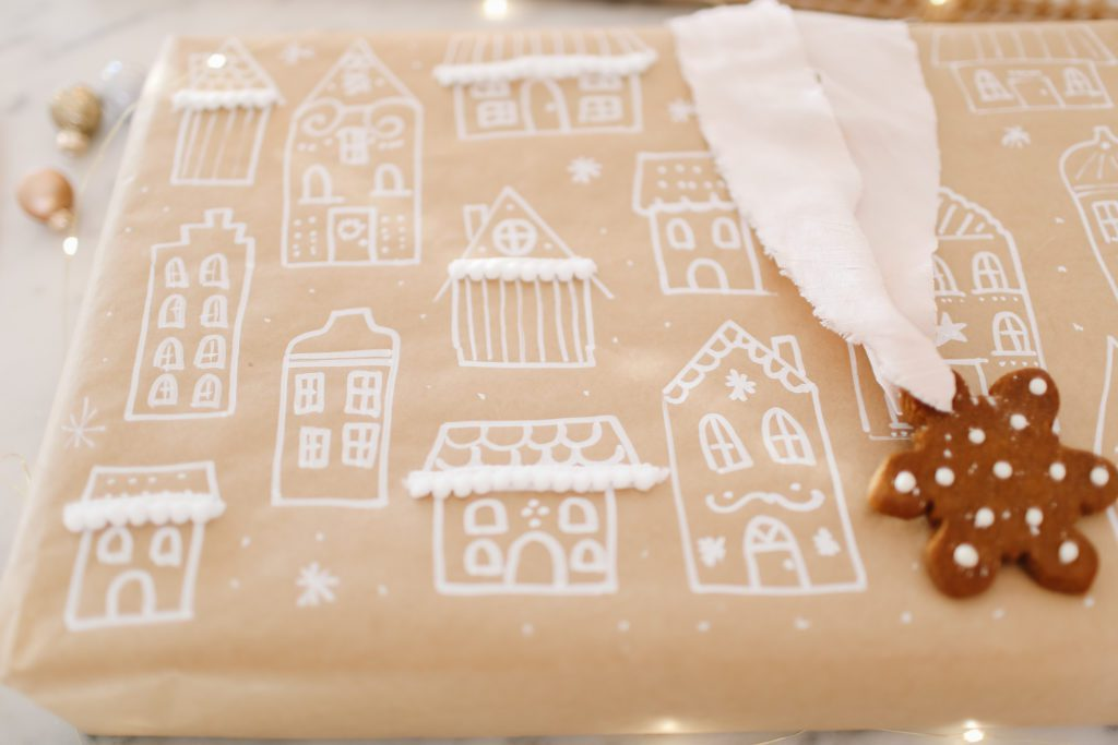 a gift wrapped in hand made gingerbread house themed paper
