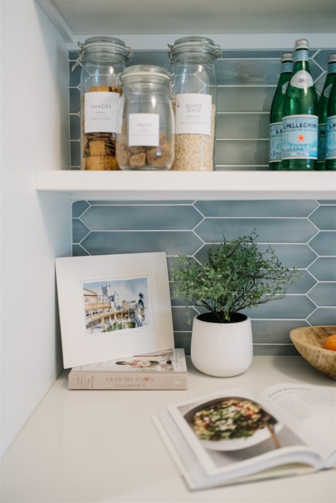 A plants and decanted staples on pantry shelves