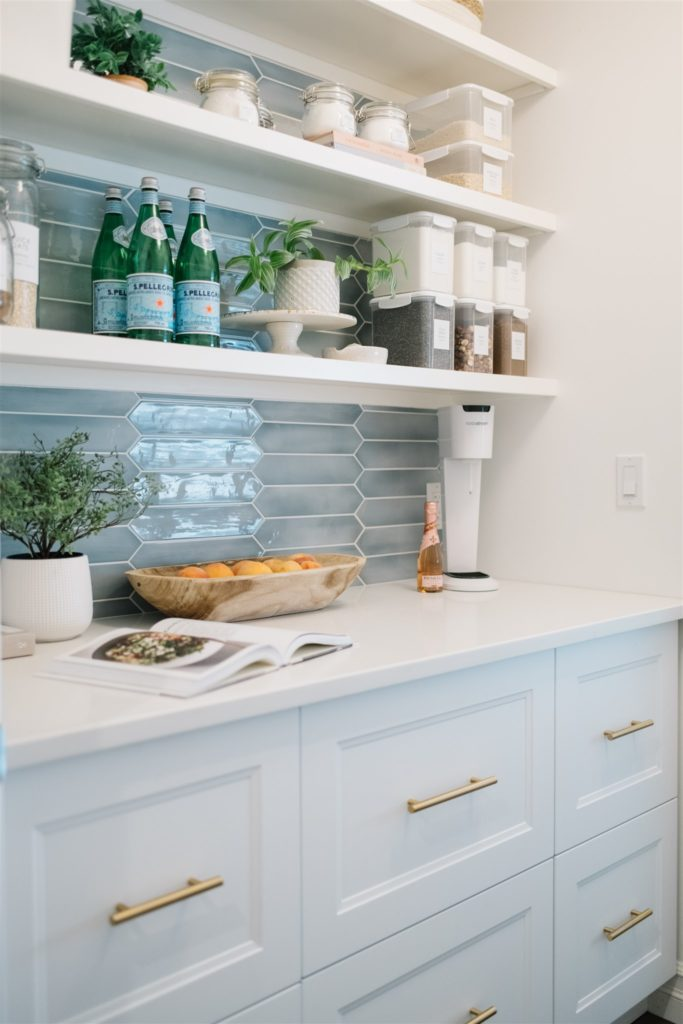 A pantry with open shelves and blue backsplash tile