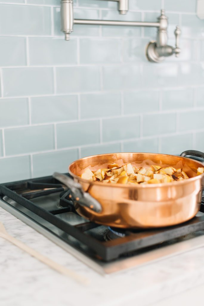 A vintage copper pot filled with apples on a stove top