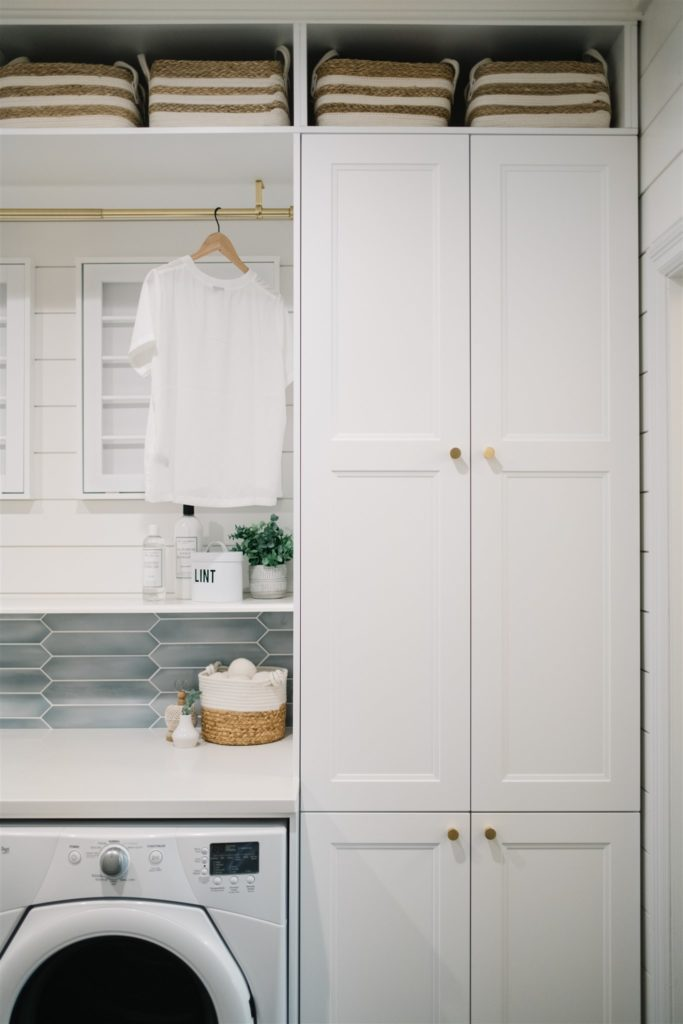 Built in laundry storage, tall white cabinets