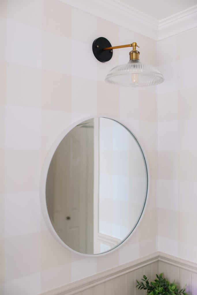 A black and brass light fixture above a round bathroom mirror