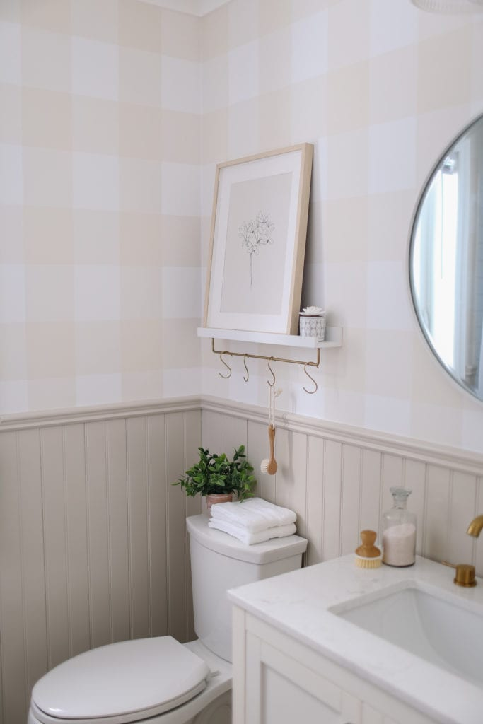 A small bathroom with a shelf above the toilet