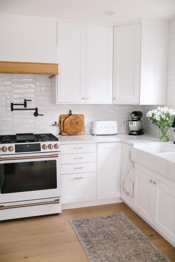 A small kitchen with white cupboards and a farmhouse sink