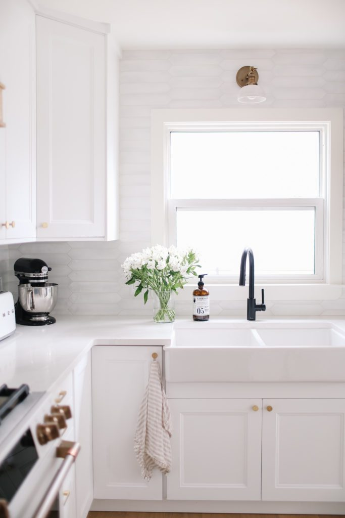 A white kitchen with a farmhouse sink and a black faucet with fresh flowers sitting beside