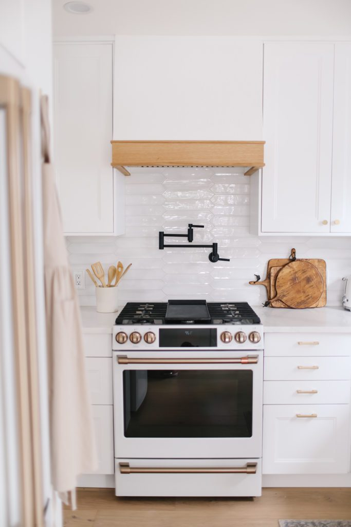 A Café Appliances stove in white and gold finishes