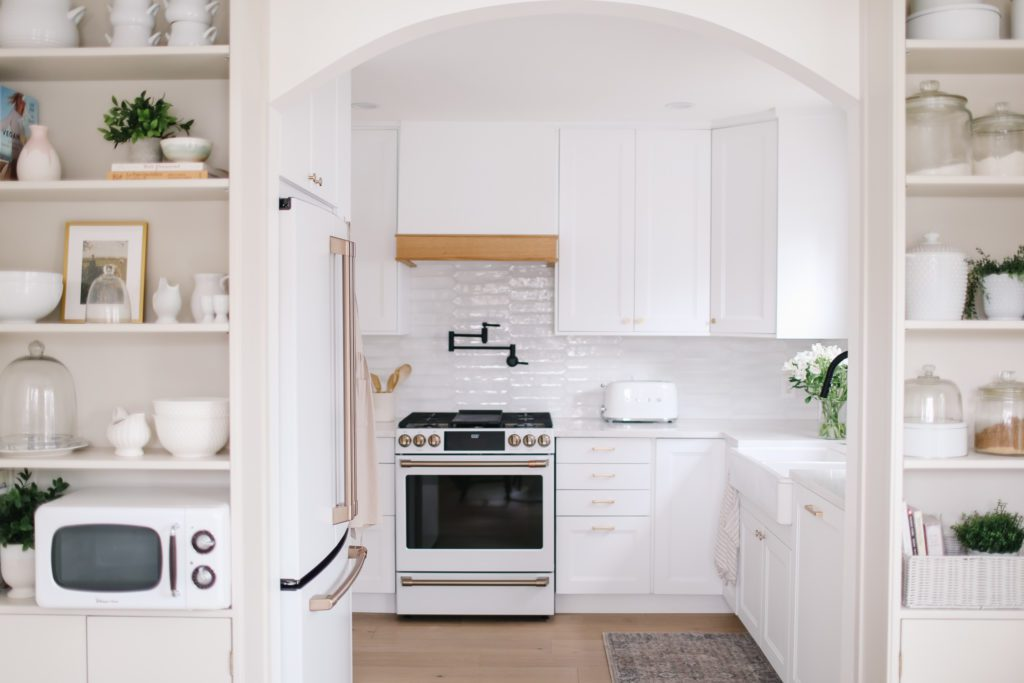 A white kitchen with a white stove and white oak trimmed hood