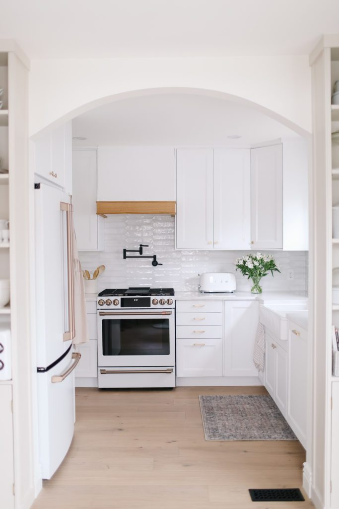 An arched opening into a small white kitchen