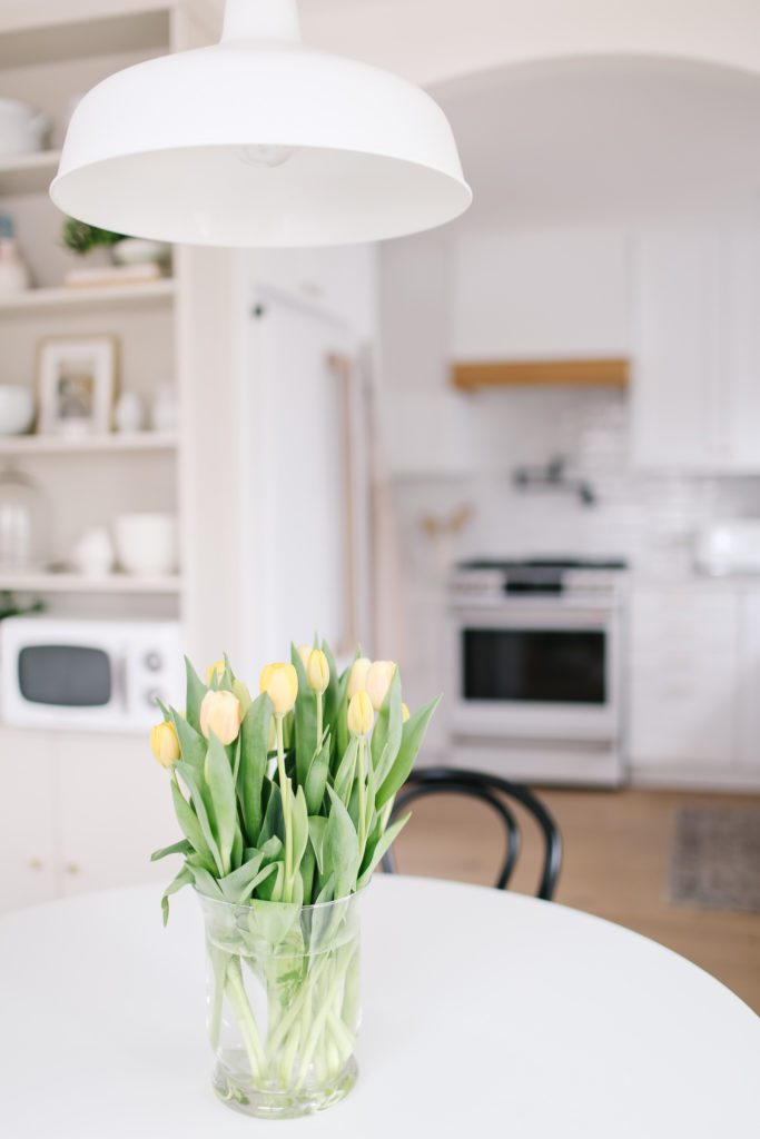 A vase of yellow tulips on a table