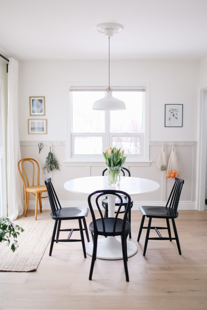 A small dining space with a round white table, black chairs and a hanging pendant light with beige panelling and a window in the wall behind.