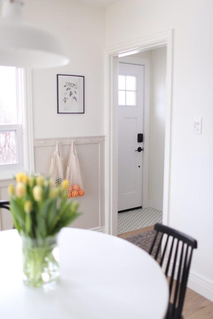 A view through the dining room to the white front door and black and white floor tile in the front entrance.