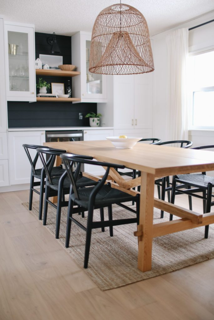 A white oak dining room table with black chairs and an oversize pendant
