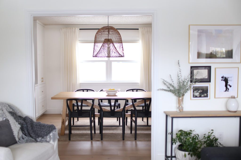 A dining room with large oversize rattan pendant