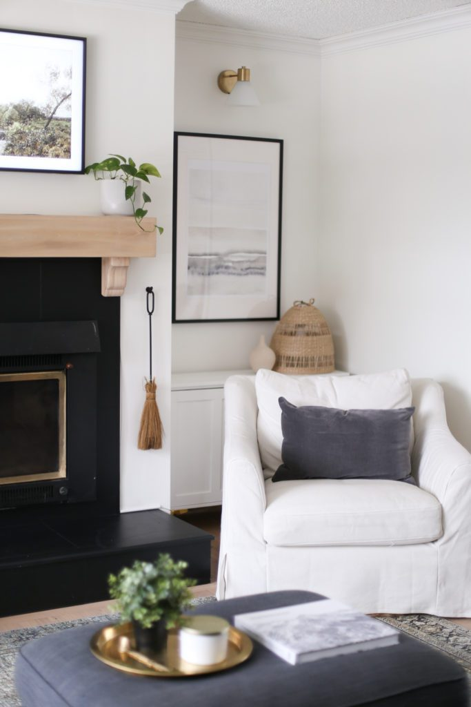 A white armchair nestled beside the wood burning fireplace with white oak mantle in the living room of a 1950s character home