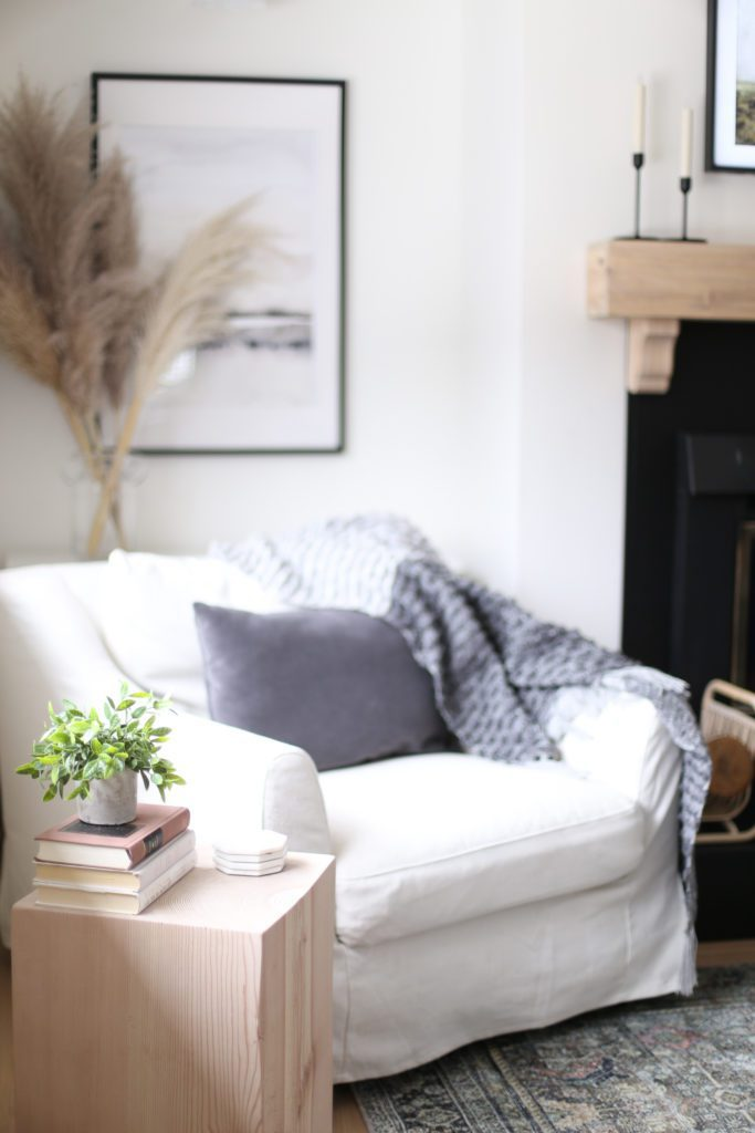 A comfy white chair with gray pillows and blankets