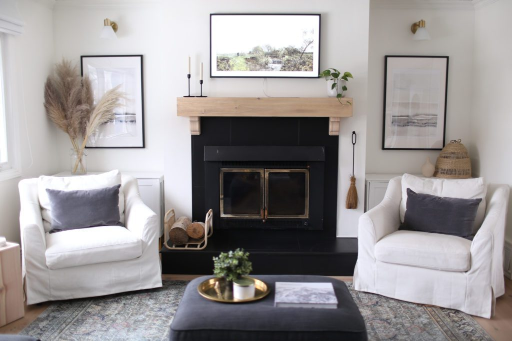 A black wood burning fireplace with white oak mantle and Samsung Frame TV mounted above