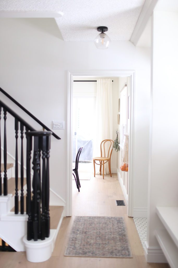 A view through to the dining room past the staircase with painted black spindles and rail.