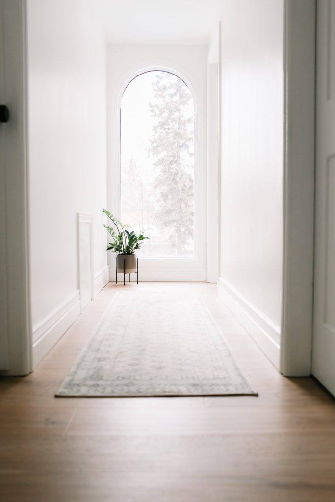 A hallway with a large window and a potted plant