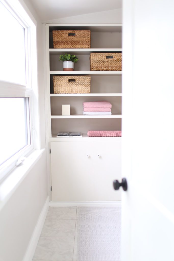 Shelves in a bathroom with baskets and pink towels