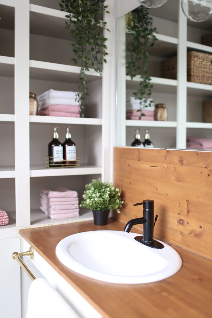 A wooden topped bathroom vanity with open shelves beside