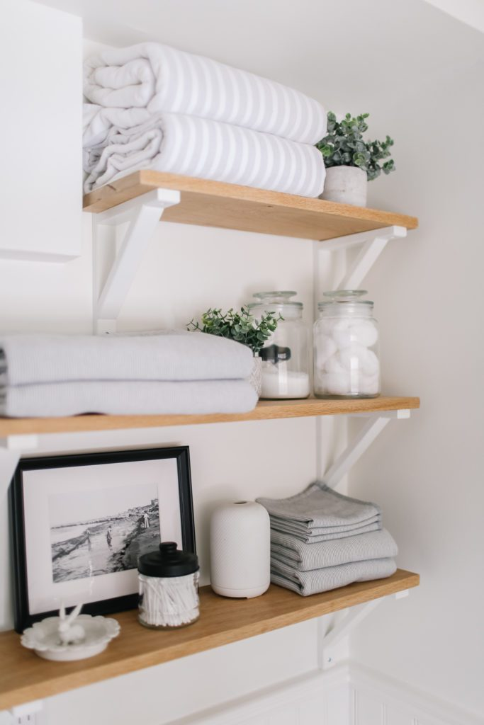 Bathroom shelves stacked with towlels and accessories