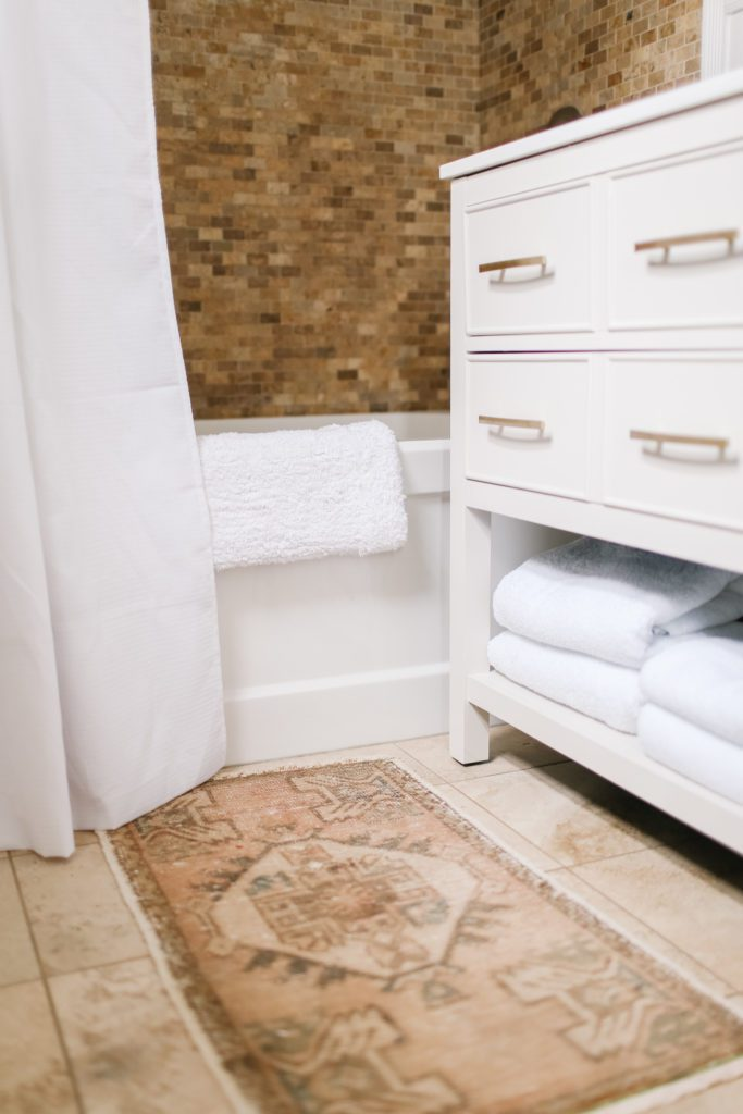 A bathroom vanity with white towels folded on the bottom shelf