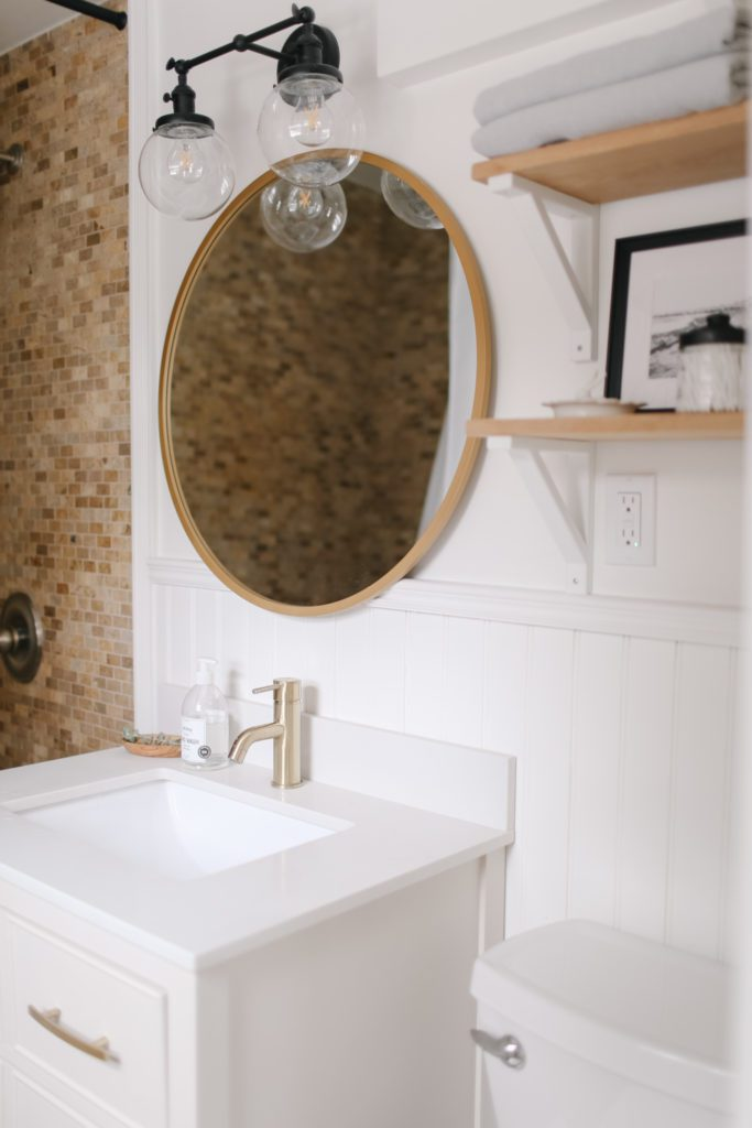 A white bathroom sink and round gold framed mirror