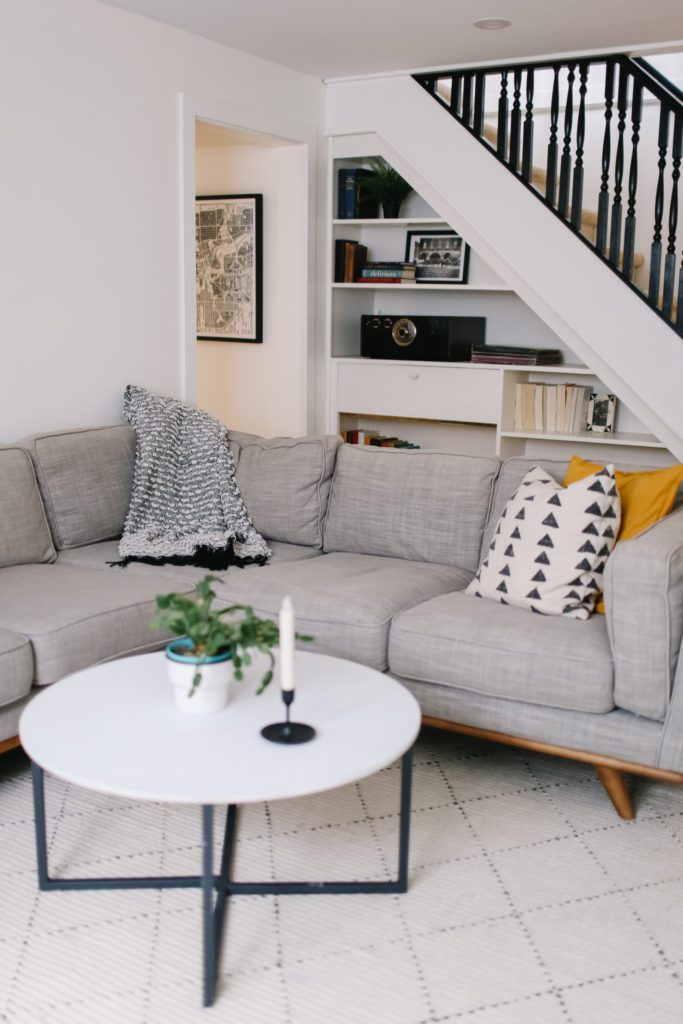 A cozy basement setup with a grey sectional, white coffee table, pillow and throws.