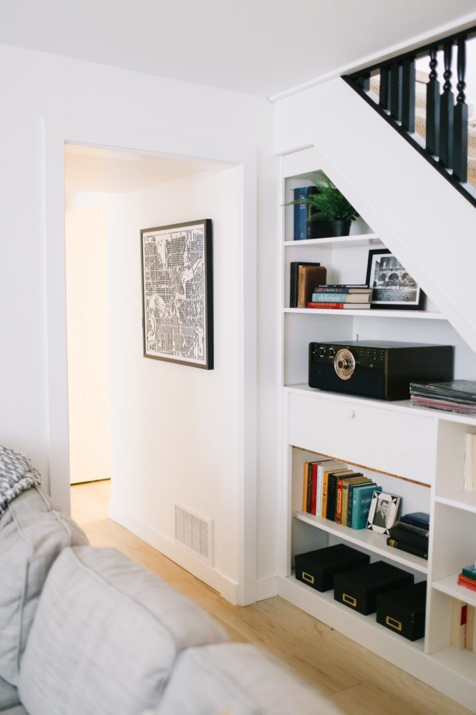 Built in shelving under the stairs with books and art