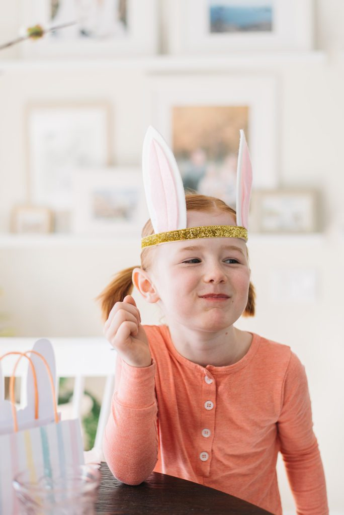 a little girl with gold and pink bunny ears