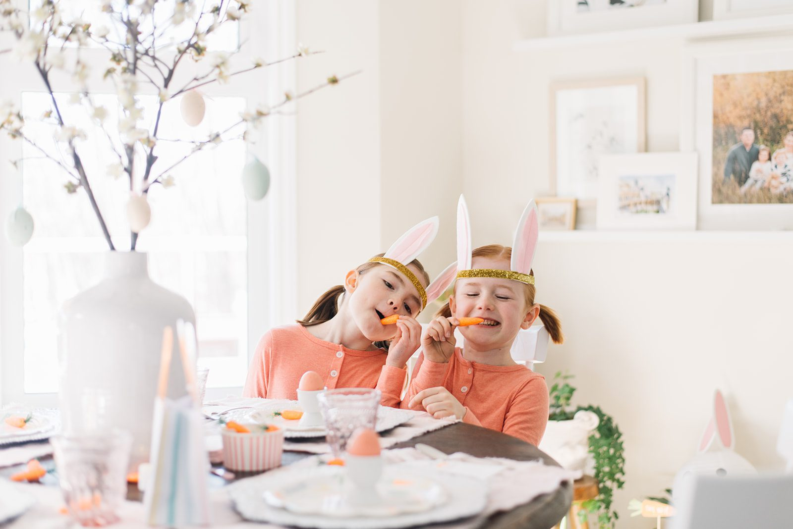 2 little girls with bunny ears sitting at a table set up Easter pretending to eat carrots