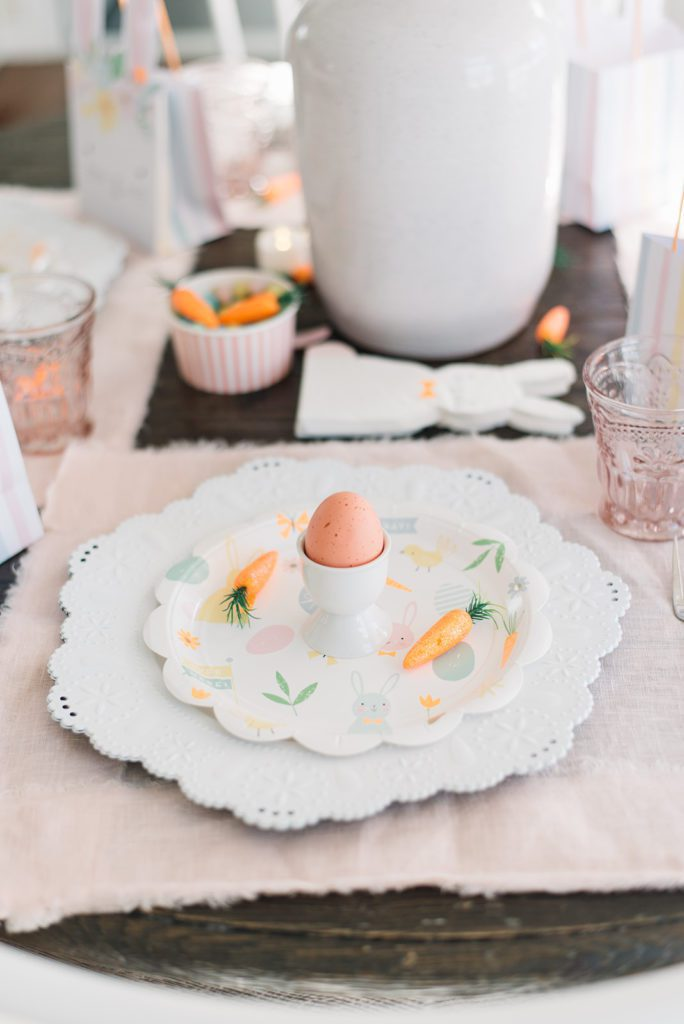A close up of an egg in an egg cup on an easter themed plate