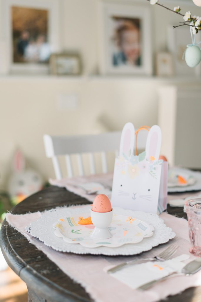 a Bunny gift bag sits behind an easter place setting on a kids easter tablescape