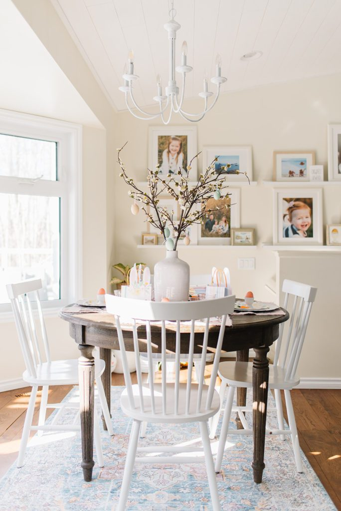 A round wooden dining room table with white chairs set up as a kids easter tablescape with bunny themed accessories